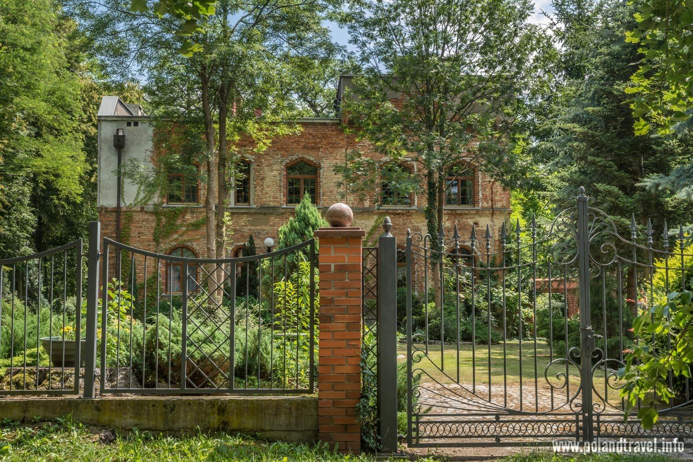 Domaszczyn, Dom Łowczego z majątku Szczodre, ceglany płot z kutymi kratami, dalej ogód i ceglany wysoki dom