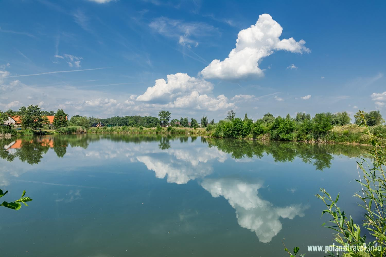Staw w Pruszowicach, z tyłu dom nad wodą , chmury odbijające się w gładkiej toni wody