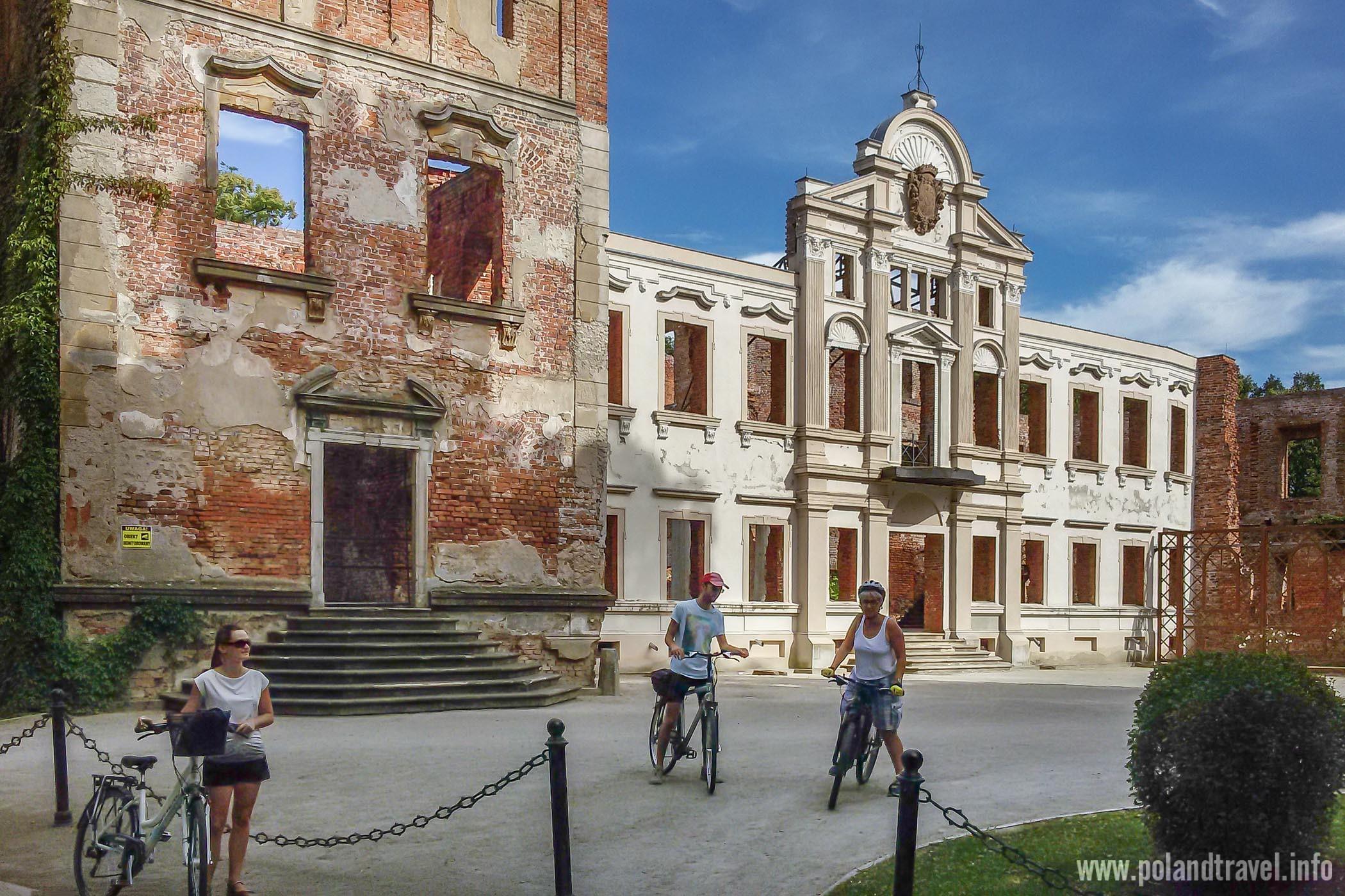 Ruiny Pałacu w Żmigrodzie, zachowana elewacja trójka rowerzystów