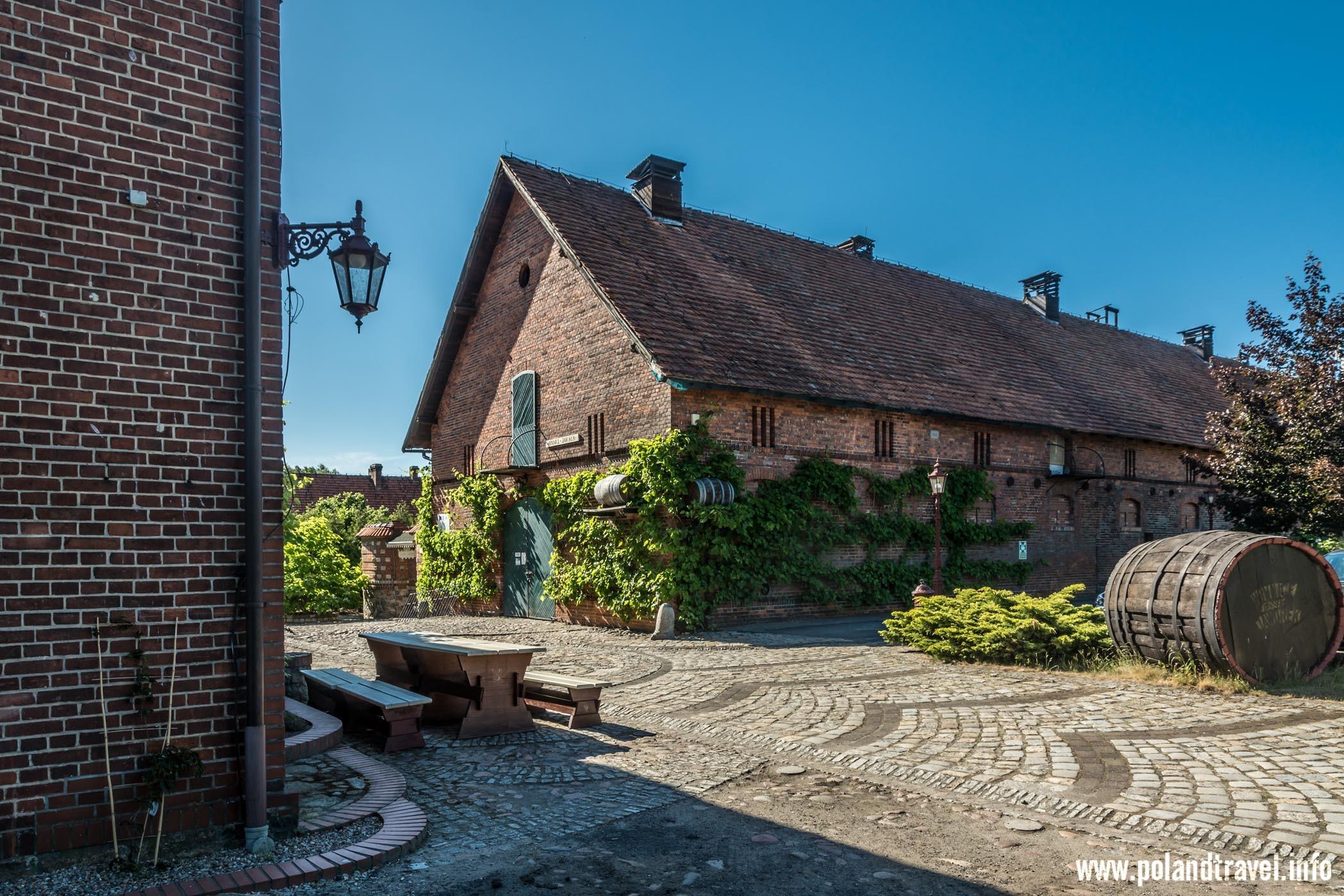 Ceglany historyczny budynek rolniczy, z przodu wielka beczka do wina, ładny bruk z przodu wraz z fragmentem budynku hotelu