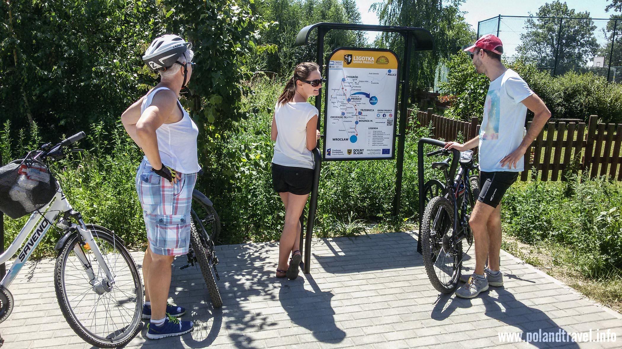 Trójka rowerzystów przed schematem ścieżek rowerowych