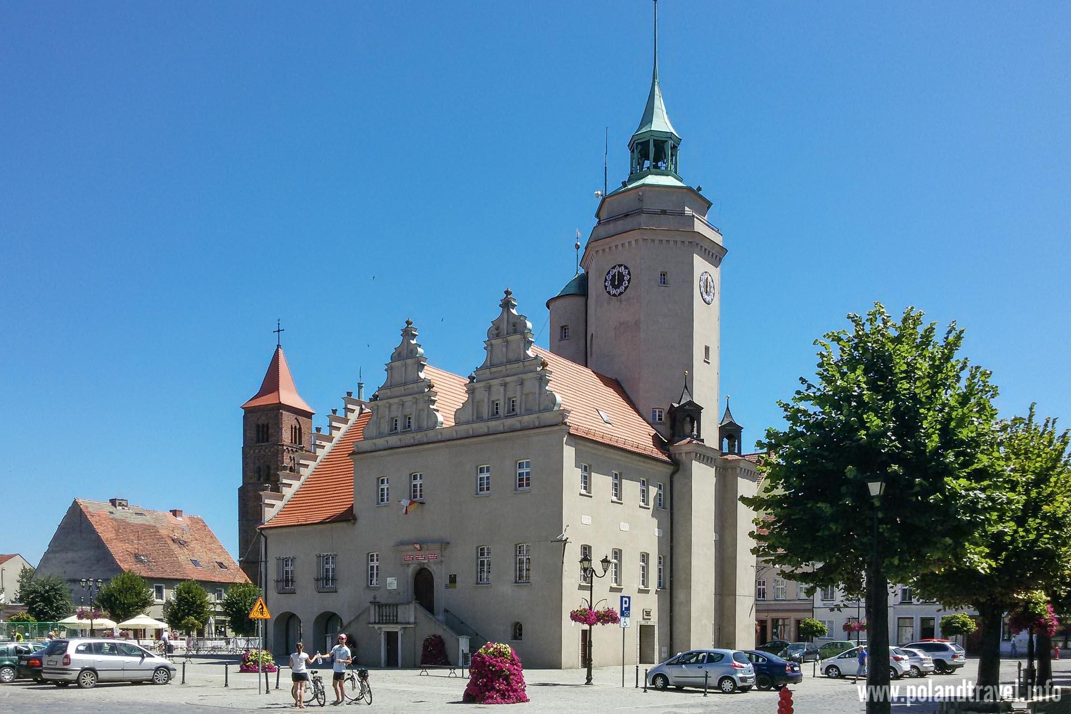 Efektowny ratusz w Prusicach w południe, w tle kościół, z boku aleja drzew