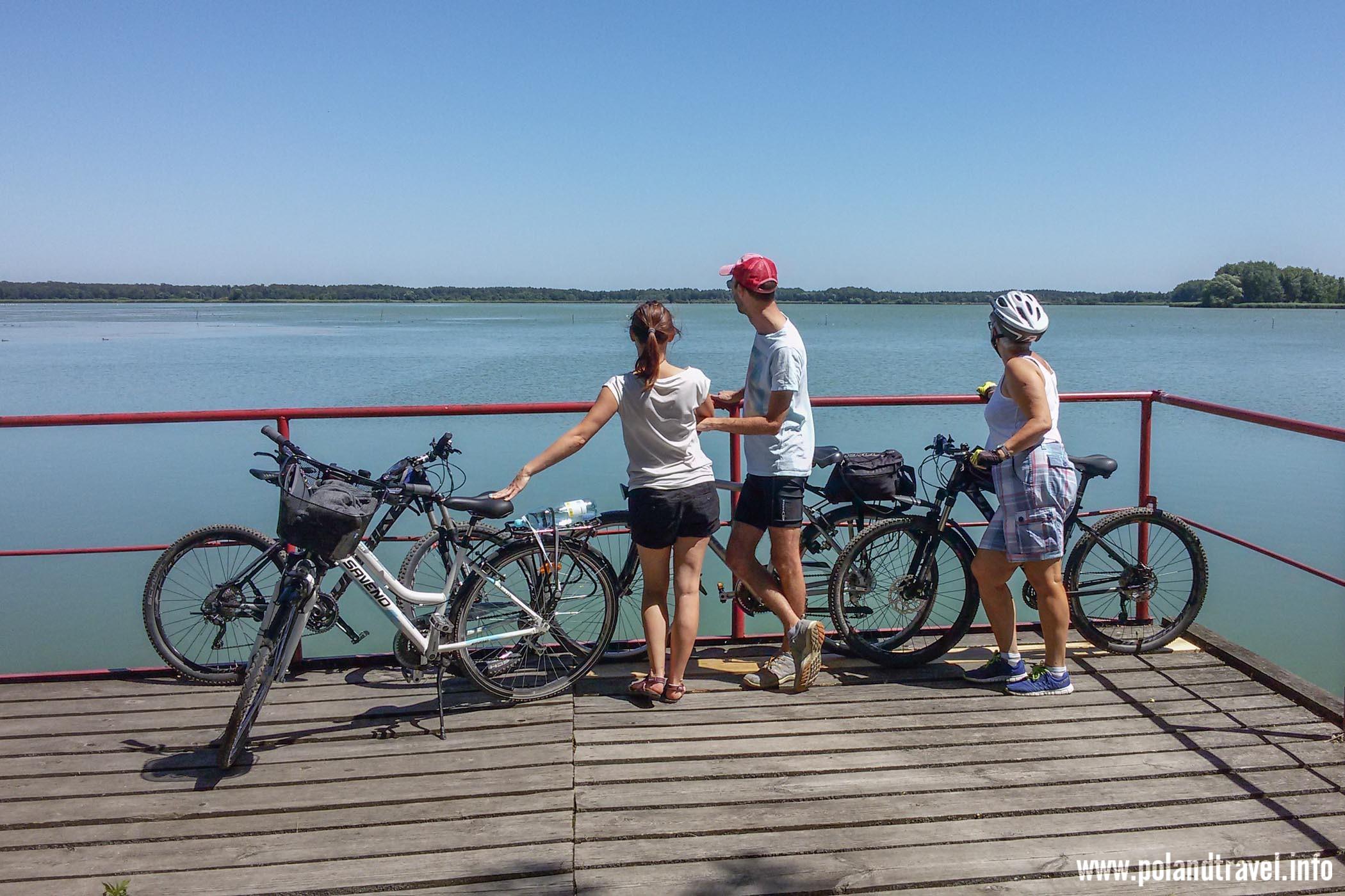 Trójka stojących rowerzystów z pojazdami przy barierce nad rozległym stawem