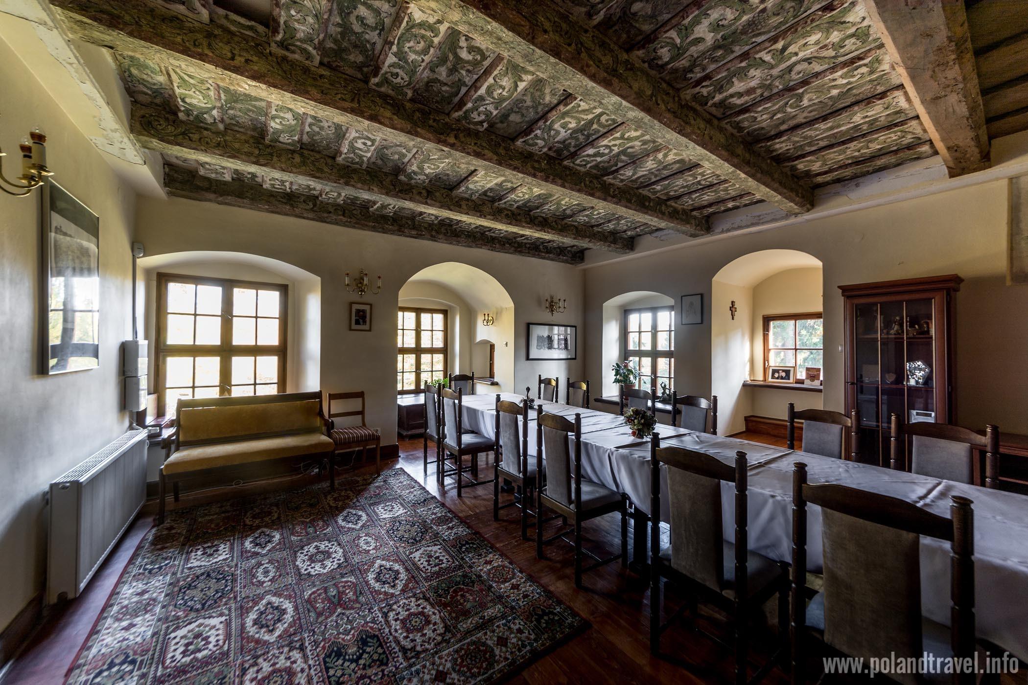 Zamek Wojnowice, Gmina Miękinia, wnętrza zamkowe, komnata z czterema oknami, długim stołem i bardzo pięknie malowanym drewnianym stropem