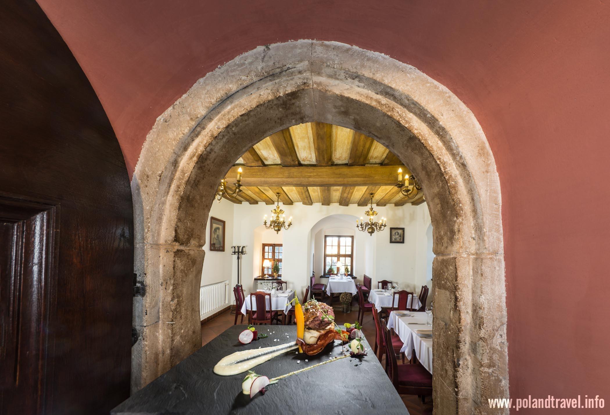 Potrawa na kwadratowym kaflu pokazana na tle zabytkowego portalu, w tle sala restauracyjna.