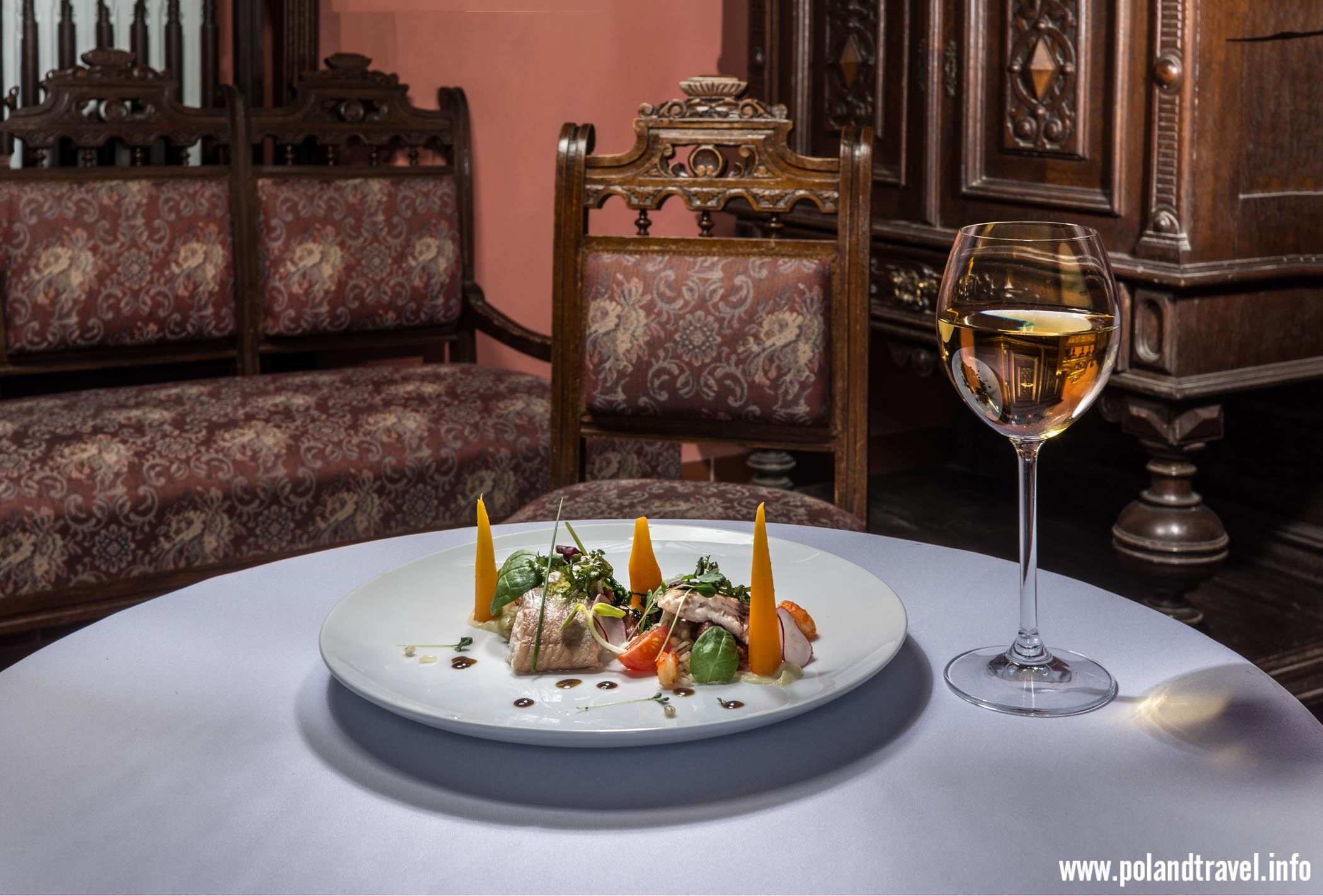 okrągły stół zasłany obrusem na nim płaski talerz z artystycznie podaną potrawą, obok kieliszek wina